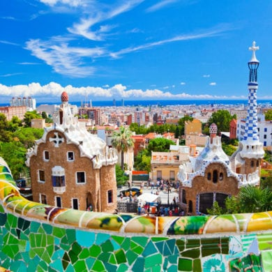 Parc Guell, Barcelona, Spain. Main entrance to Gaudi's Parc Guell and skyline of Barcelona. istock.com/eli_asenova